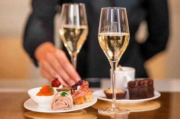 [Translate to Englisch:] Auf einem Tisch stehen zwei kleine Teller mit Canapés und zwei Gläser Champagner