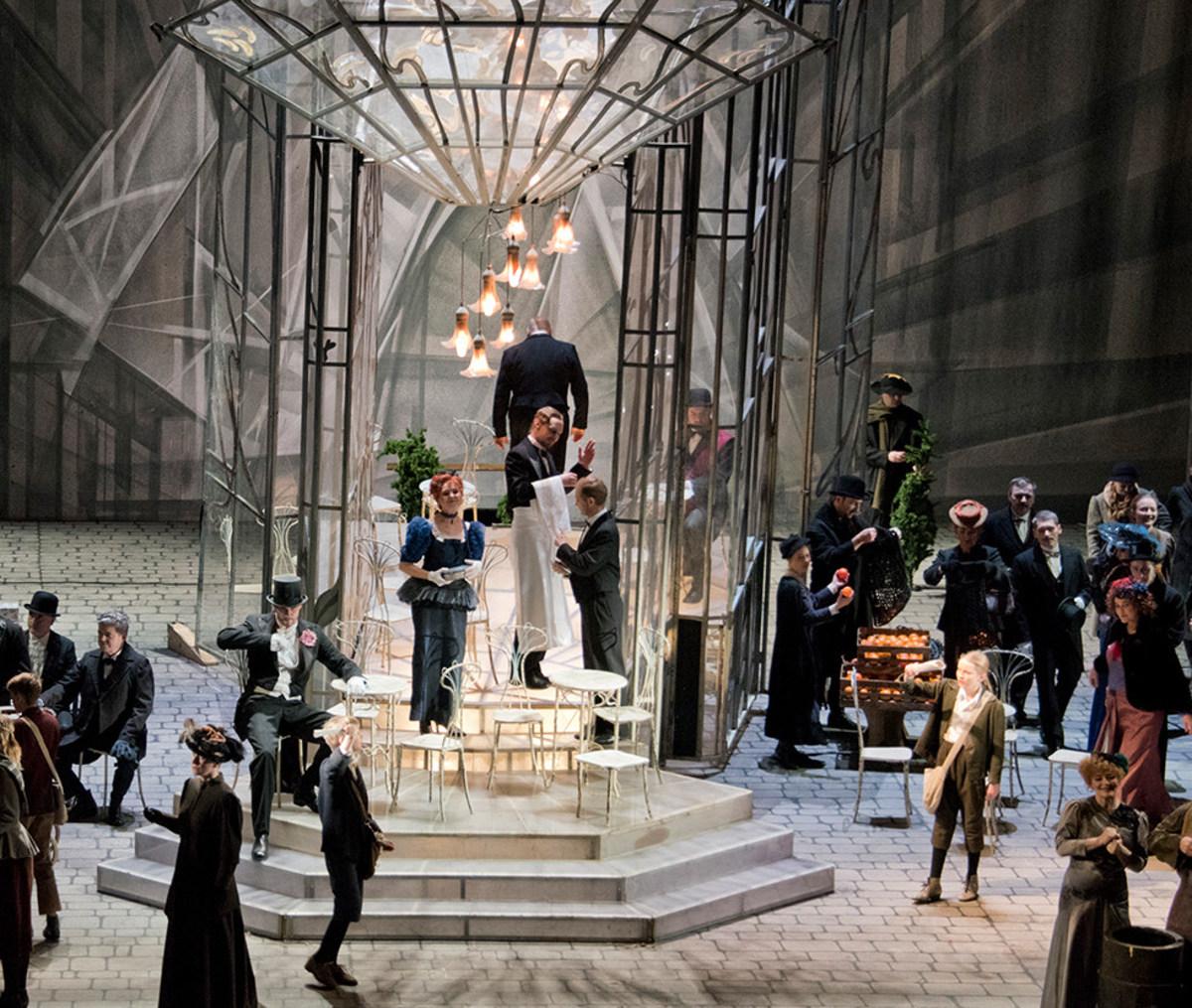 """Szene aus """"La Bohème"""": Mittig steht ein gläserner Kasten, drinnen und draußen stehen Café-Stühle. Einige wenige Sänger*innen befinden sich im Kasten, der Großteil steht außerhalb"""