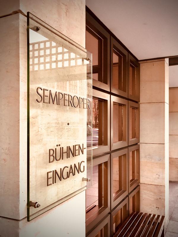 Transparentes Schild auf einer Sandsteinmauer mit goldenem Schriftzug Semperoper Bühneneingang