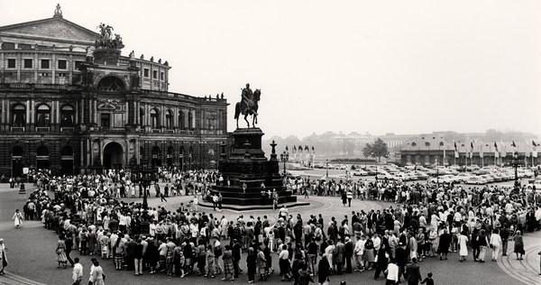 Zahlreiche Menschen versammeln sich auf dem Theaterplatz vor der Semperoper rund um die König-Johann-Statue, einen Reiter auf einem Sockel