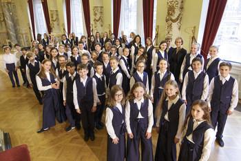 Mädchen und Jungen in dunkelblauen Hosenanzügen und weißen Hemden stehen in einer Gruppe zusammen und schauen nach oben in die Kamera