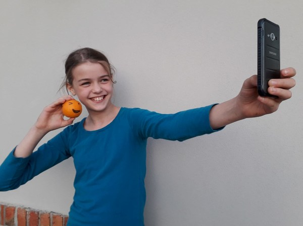 Lachendes Mädchen im blauen Pullover mit Orange in der Hand macht ein Selfie mit dem Smartphone.