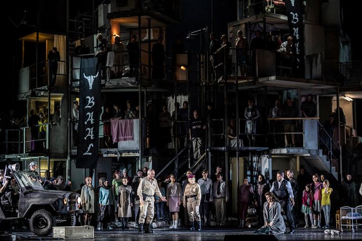 Szene aus der Oper »Nabucco« mit vielen Menschen auf einer Stahlkonstruktion, im Vordergrund ein Mann und zwei Frauen im Disput, eine der Frauen kniet auf dem Boden