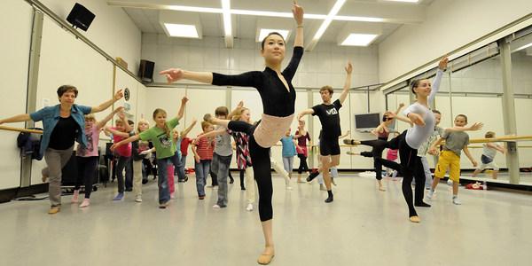 Junge Frau tanzt Ballettfiguren vor und Kinder tanzen diese nach