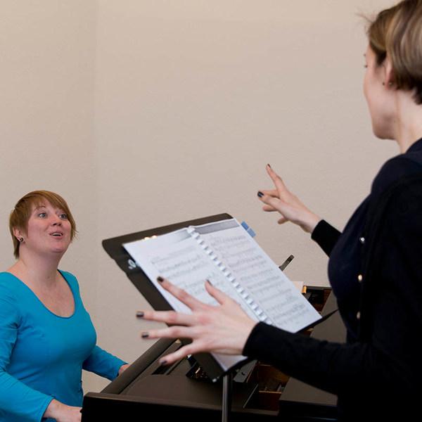 Frau am Klavier probt Gesang mit einer Frau vor einem Notenständer mit Notenblättern