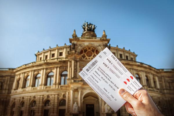 Eine Hand hält Eintrittskarten für die Semperoper in die Höhe, im Hintergrund ist die Semperoper zu sehen