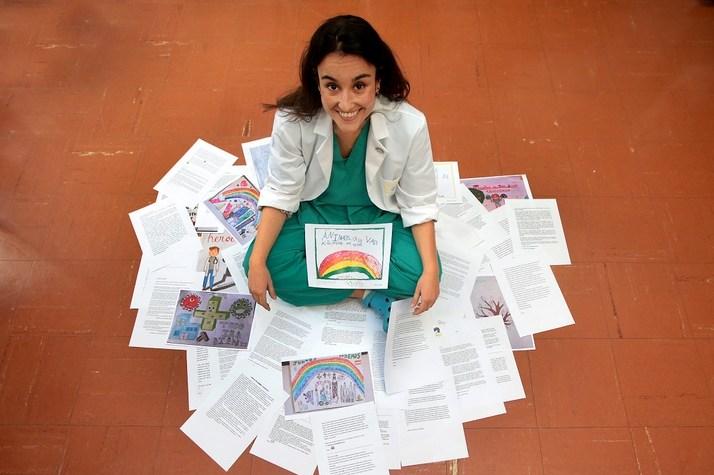 Ärztin sitzt lächelnd auf dem Boden zwischen ausgebreiteten Briefen