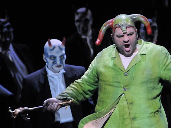 """Szene aus """"Rigoletto"""": Sänger in grünfarbenem Kostüm steht vor weiteren Sängern"""