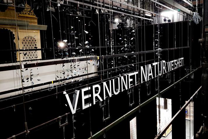 """[Translate to Englisch:] Schriftzug """"Vernunft, Natur, Weisheit"""" in Neonbuchstaben, in Gerüst hängend"""
