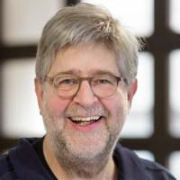Lachender Mann in dunkelblauem Hemd mit graumelierten Haaren und Brille