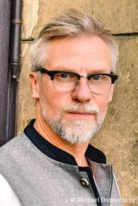 Ein Mann in weißem Hemd und grauer Weste mit kurzen, graumelierten Haaren und Brille