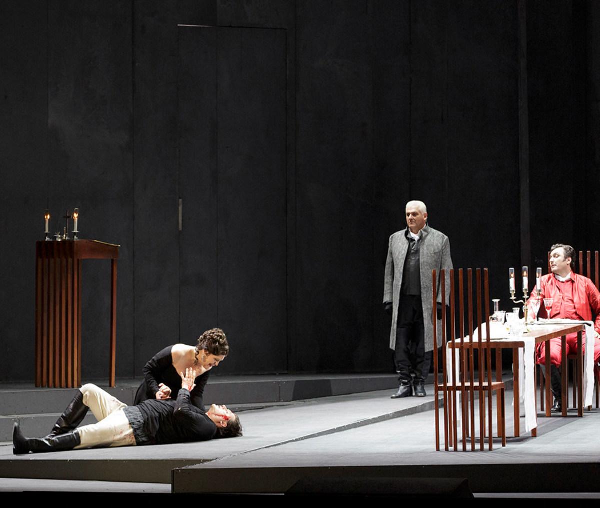 """Szene aus """"Tosca"""": Sängerin kniet neben liegendem Sänger und hält seine Hand, im Hintergund befinden sich 4 weitere Sänger"""