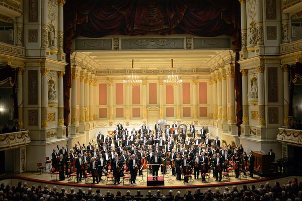 Musikerinnen und Musiker stehen mit ihren Instrumenten in der Hand zusammen mit dem Dirigenten auf der Bühne der Semperoper und blicken ins Publikum