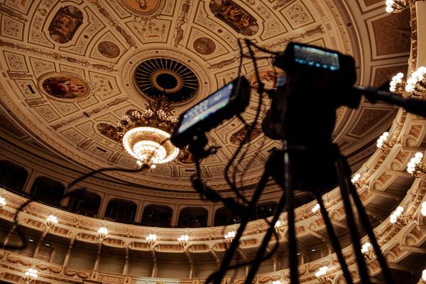Zuschauerraum der Semperoper mit Kronleuchter und Filmkamera im Vordergrund