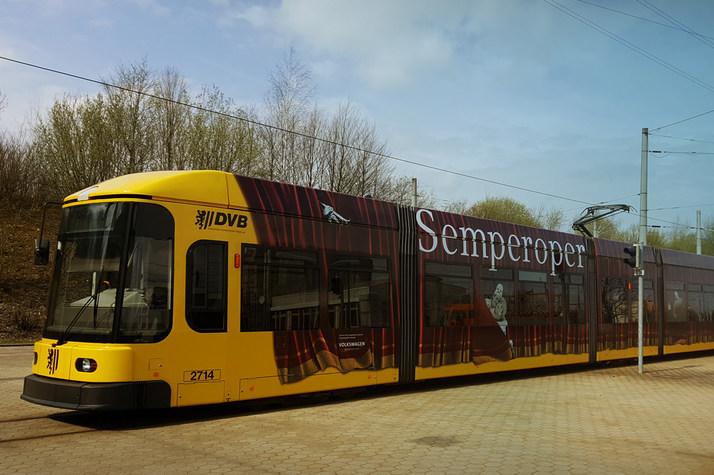 Gelbe Straßenbahn mit rotem Vorhang und Schriftzug »Semperoper« als Werbeaufdruck