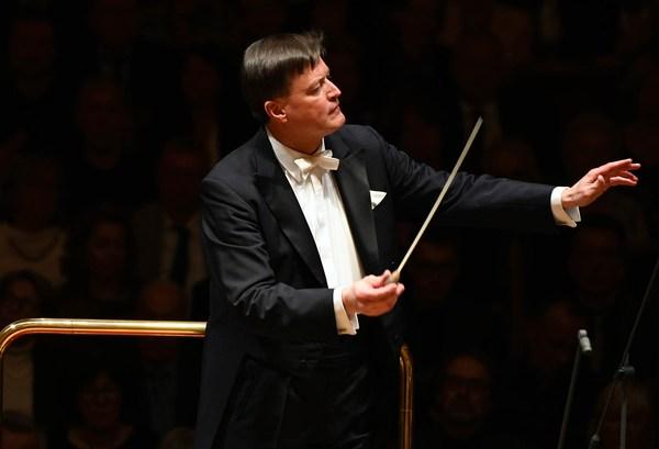 Mann im schwarzen Frack mit Taktstock in der Hand dirigiert lächelnd ein Orchester