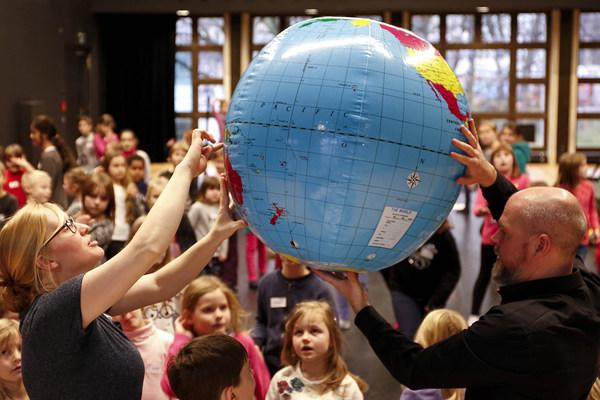 Eine Frau und ein Mann halten vor einer Gruppe Kinder einen Wasserball als Weltkugel hoch