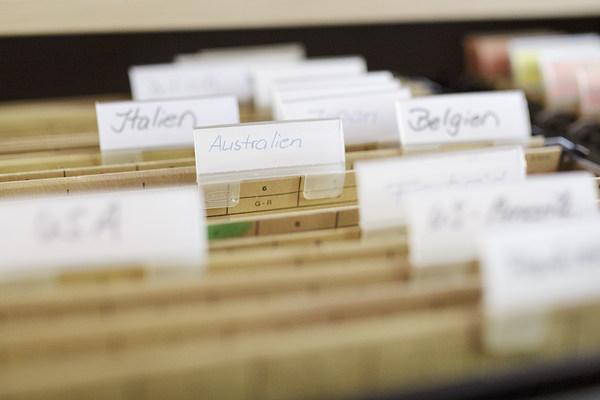 Nahaufnahme von Registermappen mit der Beschriftung Italien, Australien und Belgien