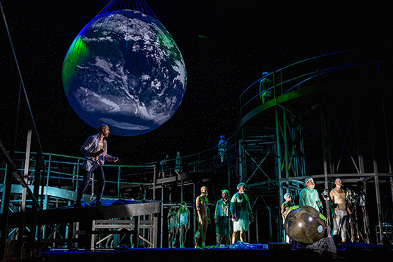 [Translate to Englisch:] Szene aus der Oper »Le Grand Macabre« mit einer riesigen über der Bühne schwebenden Erdkugel, darunter ein geschwungener Steg mit den Sängerinnen und Sängern