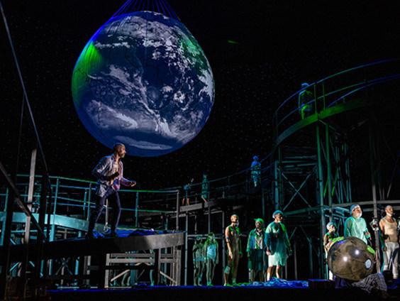 Szene aus der Oper »Le Grand Macabre« mit einer riesigen über der Bühne schwebenden Erdkugel, darunter ein geschwungener Steg mit den Sängerinnen und Sängern