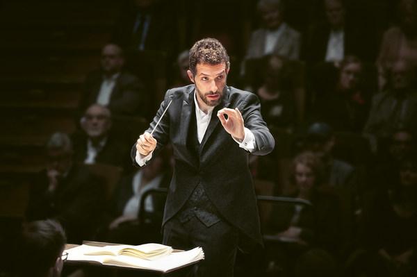 Dirigent im schwarzen Anzug mit erhobenem Taktstock schaut konzentriert ins Orchester, im Hintergrund ist verschwommen Publikum zu sehen