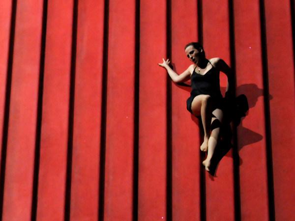 """Szene aus """"La traviata"""": Sängerin liegt rechts im Bild auf schräger, rotfarbener Ebene"""