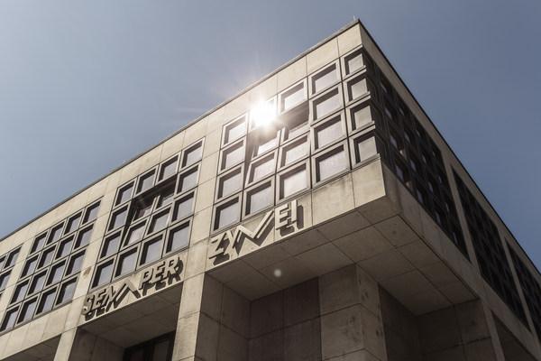 Die Spielstätte Semper Zwei, ein Sandsteinwürfel mit großen braunen Fenstern aus 4x4 Quadraten, in einer dieser Scheiben spiegelt sich die Sonne