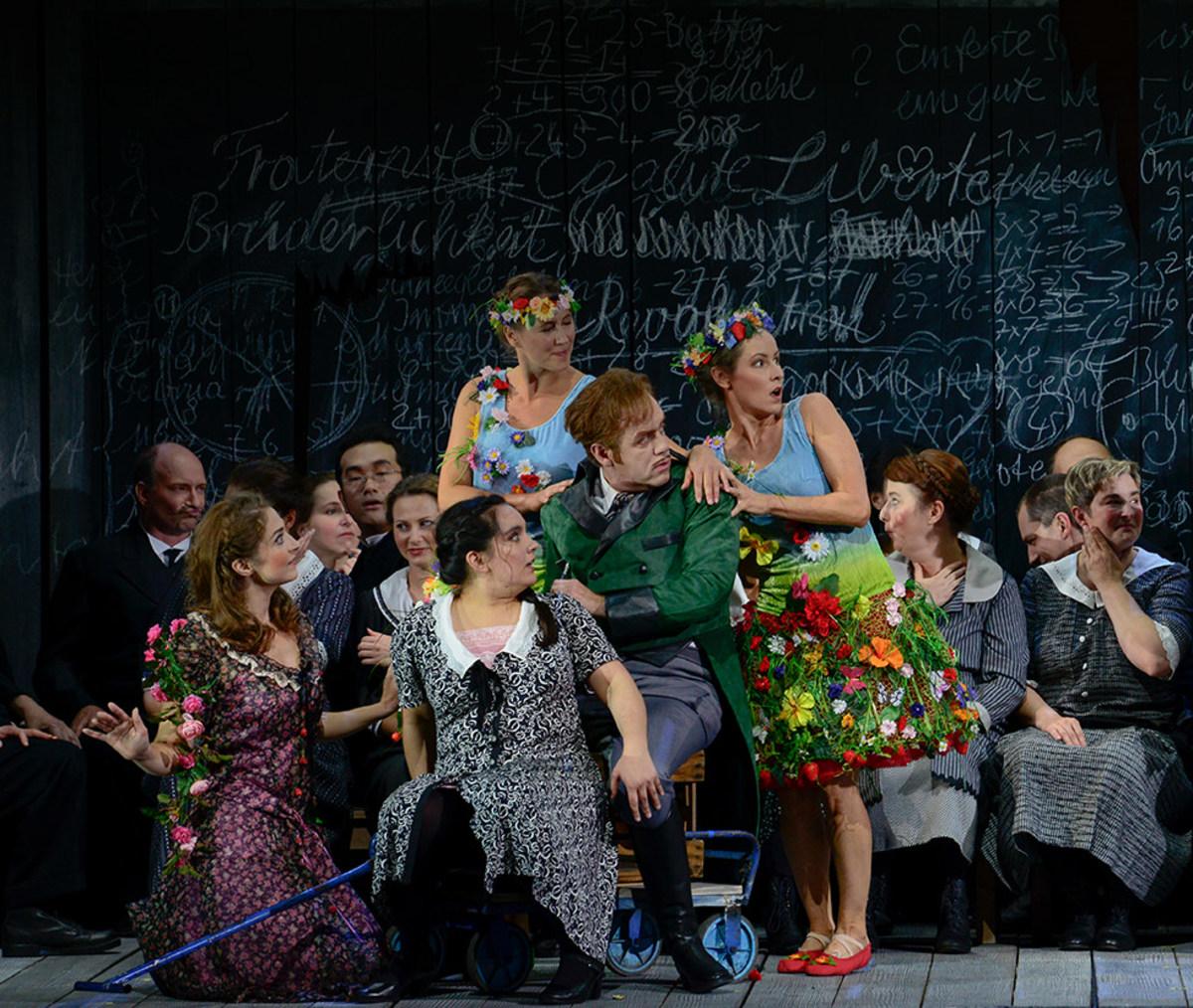 """Szene aus """"Der Wildschütz"""": Recht und links sind zwei Sänger, der rechts Sitzende ist umringt von 4 Sängerinnen"""