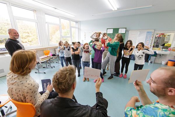 Schüler*innen und Erwachsene in einem Klassenraum improvisieren Begriffe und Stimmungen, die auf Zettel geschrieben und hochgehalten werden