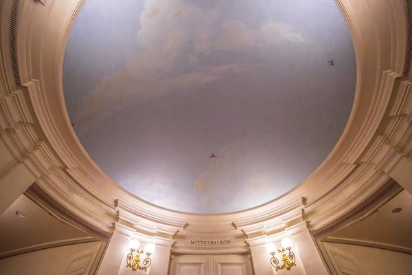 Mit blassblauem Himmel, weißen Wolken und kleinen Vögeln bemalte Decke vor dem Mittelbalkon im Foyer der Semperoper