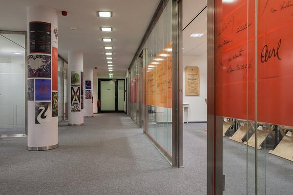 Raum mit links plakatierten Säulen und rechts Trennwänden aus Glas, an die Faksimiles von Unterschriften geklebt sind