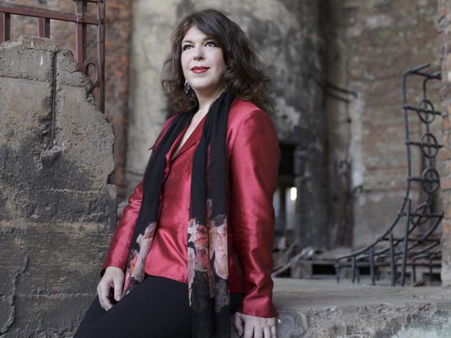 Frau mit eleganter roter Bluse sitzt lächelnd auf den Steinen einer Kirchenruine