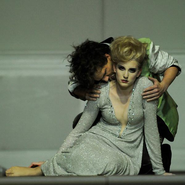 Szenenfoto der Oper »Alcina« mit einer auf dem Boden sitzenden blonden Frau im glitzernden Kleid, die von einem schwarzhaarigen Mann von hinten an den Schultern gepackt und auf eine Schulter geküsst wird