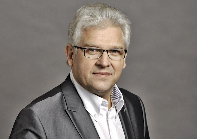 Ein Mann mit grauen Haaren und Brille mit weißem Hemd und anthrazitfarbenem Anzug lächelt in die Kamera
