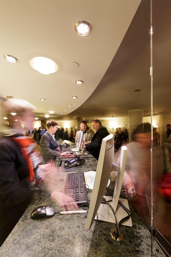 [Translate to Englisch:] Zwei Mitarbeiterinnen der Semperoper bedienen an der Abendkasse Kunden an einem Tresen mit Granitplatte, auf dem zwei Monitore, zwei Computertastaturen, zwei Computermäuse und zwei EC-Karten-Lesegeräte stehen