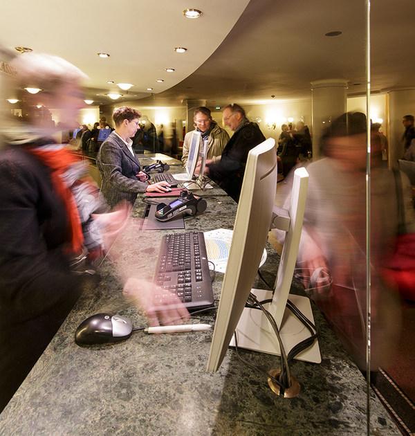 Zwei Mitarbeiterinnen der Semperoper bedienen an der Abendkasse Kunden an einem Tresen mit Granitplatte, auf dem zwei Monitore, zwei Computertastaturen, zwei Computermäuse und zwei EC-Karten-Lesegeräte stehen