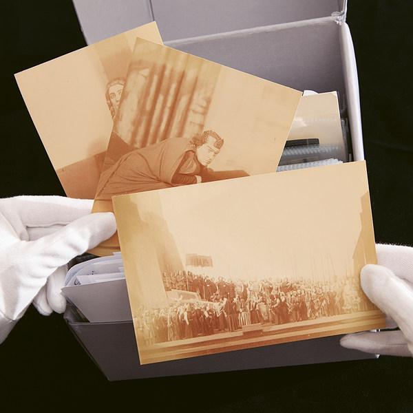 Zwei Hände mit weißen Handschuhen heben drei historische, sepia-farbene Fotografien aus einer Papp-Box