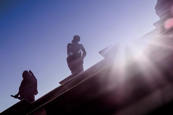 Sandstein-Figuren vor blauem Himmel und Sonnenschein auf einem Dachsims