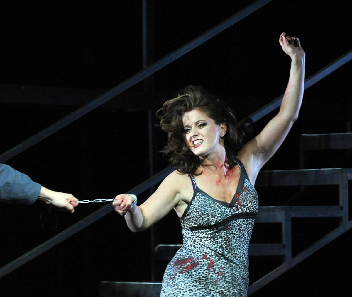 """Szene aus """"Carmen"""": Ein Handgelenk einer Sängerin ist in in Handschellen. Sie zieht an der damit verbundenen Kette, die von einem Sänger festgehalten wird"""