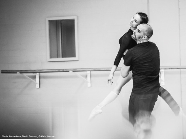 Ein Mann in schwarzer Hose und schwarzem T-Shirt hebt eine Tänzerin an der Hüfte nach oben