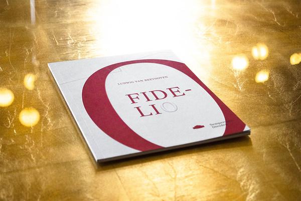Ein rot-weißes Programmheft mit dem Titel »Fidelio« liegt auf goldenem Untergrund