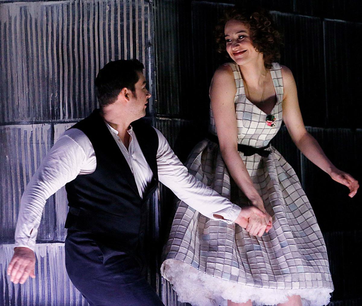 """Szene aus """"Cavalleria rusticana"""": Ein Sänger und eine Sängerin halten sich die Hand und lächeln sich an"""