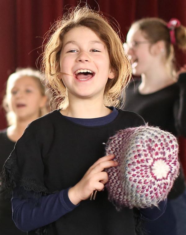 Lachendes Mädchen mit Wollmütze in der Hand