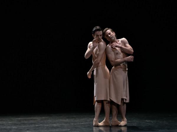Zwei Ballettänzer in apricot-farbenen Röcken stehen Rücken an Rücken auf der Bühne