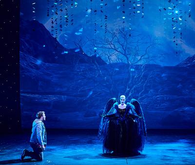 """Szene aus """"Die Zauberflöte"""": Sängerin steht mittig auf der Bühne, ein Sänger kniet links neben ihr"""