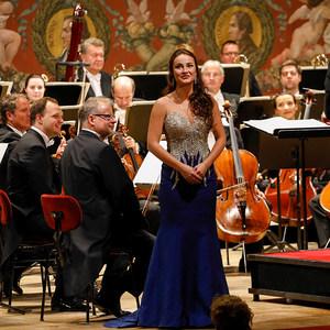 Sängerin im schulterfreien, silber-dunkelblauen Kleid steht vor den Orchestermusikerinnen und Orchestermusikern auf der Bühne der Semperoper