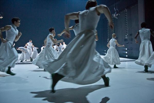 Tänzer und Tänzerinnen in weißen Röcken rennen über die Bühne