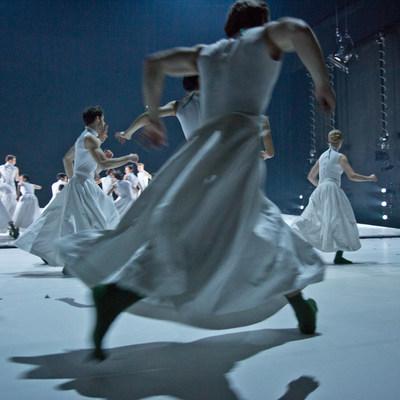 Ein Tänzer rennt in weißem Shirt und weißem Rock mit dem Rücken zur Kamera, im Hintergrund weitere Tänzerinnen und Tänzer in weißen Kostümen