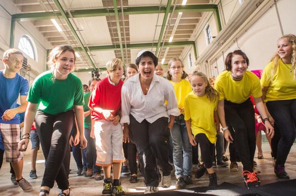 Eine Gruppe Jugendlicher läuft in gebückter Haltung lachend auf die Kamera zu