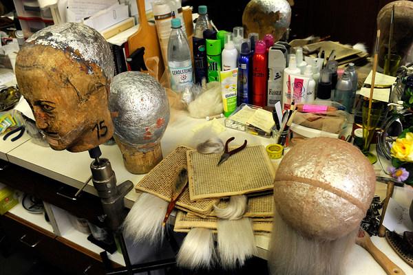 Tisch mit Holzmodellen von Köpfen, Haarteilen für Perücken, Bürsten und Zangen, Haarsprays und weiteren Haarpflegeprodukten
